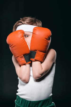 boy obscuring face with boxing gloves isolated on black