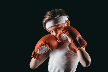 obscuring: boy obscuring face with boxing gloves isolated on black