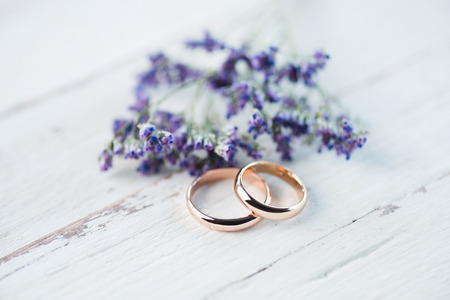 golden wedding rings and beautiful small blue flowers on wooden tabletop