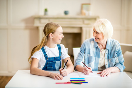grandmother and granddaughter drawing together and smiling each other