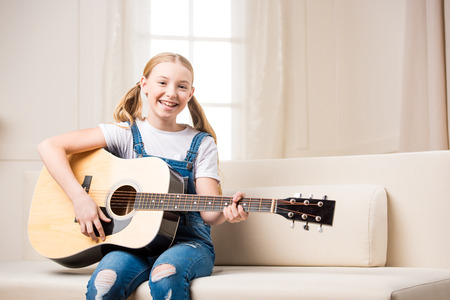 smiling girl sitting on sofa and playing acoustic guitar Imagens