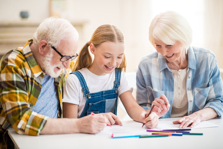 girl with grandfather and grandmother sitting at table and drawing together