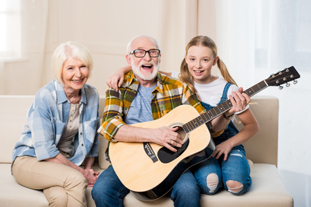 happy girl with grandparents sitting together on sofa and playing acoustic guitar