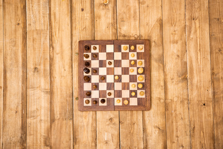 wooden chessboard with pieces on brown wooden planks