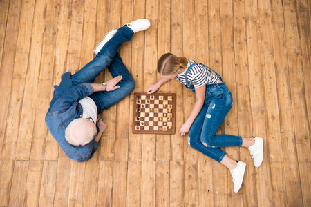 grandfather and granddaughter playing chess on hardwood floor