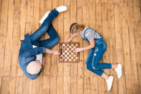 grandfather and granddaughter playing chess on hardwood floor Фото со стока - 78915639
