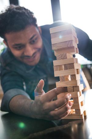 man playing wooden block game Stock Photo