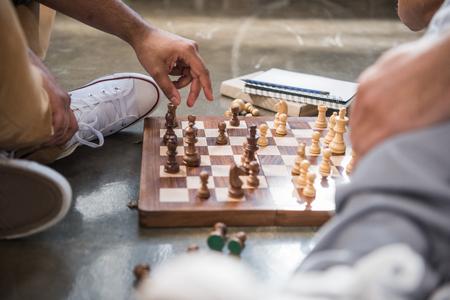 若い男性の床に座って、チェスボード上のチェス