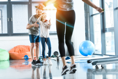 fitness people exercising with skipping ropes at sports center