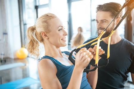 Coach praten met blonde fitness vrouw training met TRX fitness bandjes