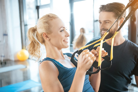 Coach talking with blonde fitness woman training with trx fitness straps