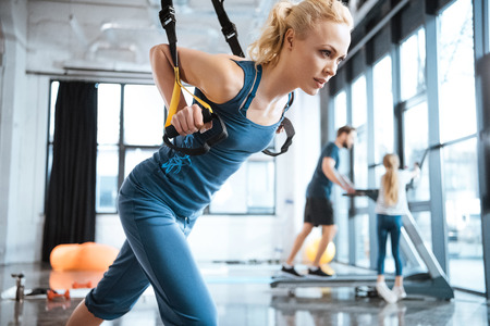 fitness woman training with trx fitness straps