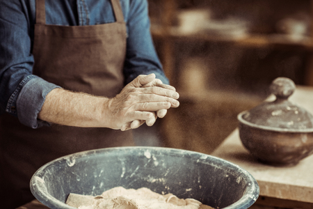 male potter hands taking clay from a bowl 版權商用圖片