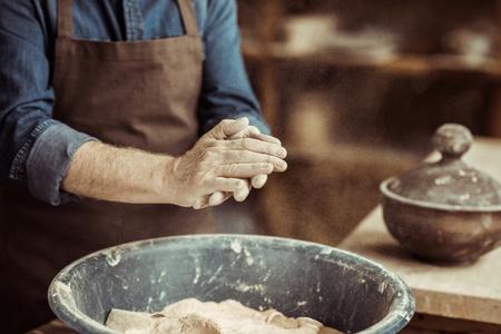 mannelijke potterhanden die klei van een kom nemen