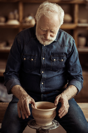 Senior potter making pottery on a wheel