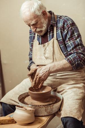 陶芸家のホイールに取り組んでいる男性の職人 写真素材