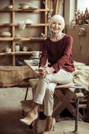 senior female potter sitting on table at workshop