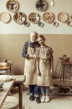 ワーク ショップに立ってエプロンで孫娘とシニア ・ ポッター 写真素材 - 79116362