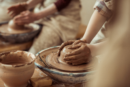 child hands working on pottery wheel at workshop Stock Photo