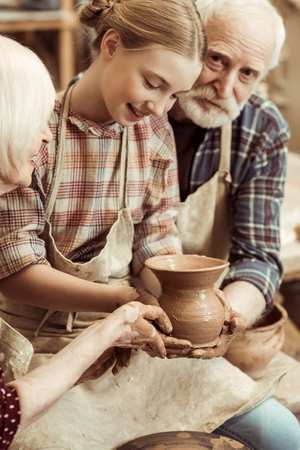 Grandmother and grandfather with granddaughter making pottery