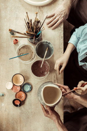 girl painting clay pot and grandparents helping at workshop