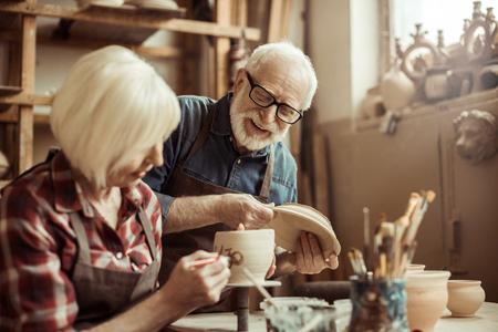 Mujer pintando olla de barro con potter senior