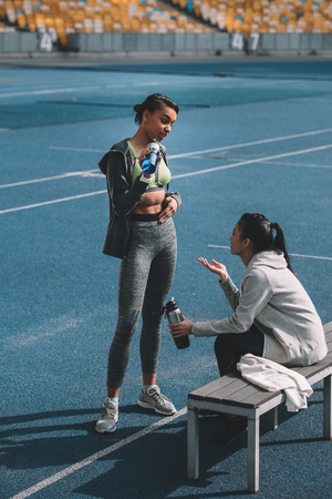 Athletic young women in sportswear drinking water from sports bottles on stadium