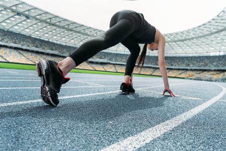 Jonge vrouw in sportkleding in uitgangspositie op renbaan stadion Stockfoto - 79234280