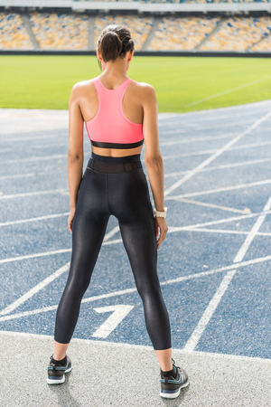 young sportswoman exercising on running track stadium