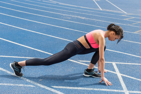 athletic young woman in sportswear on starting line ready to run Stock Photo
