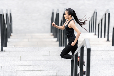 attractive young asian woman in sportswear jogging on stadium stairs