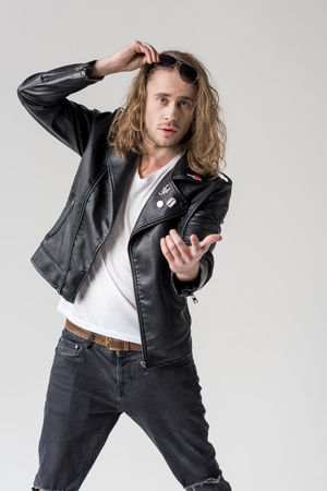 young handsome man in black leather jacket pointing isolated