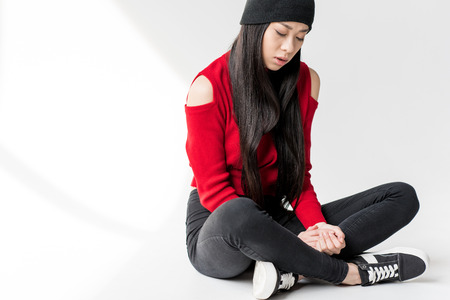 attractive asian woman sitting and looking down