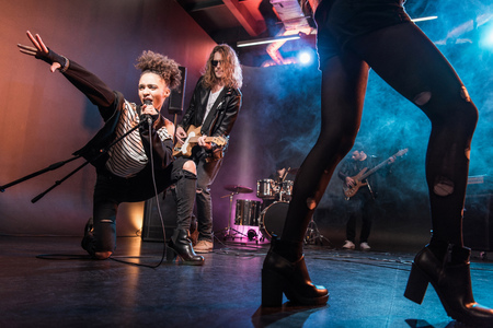 multiethnic rock and roll band performing concert on stage
