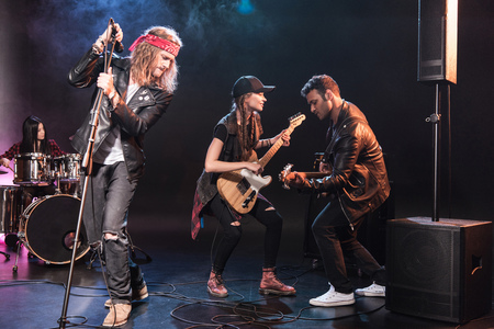 multiethnic rock and roll band performing music on stage
