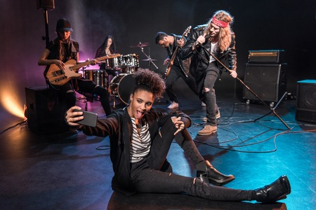 woman taking selfie with rock and roll band performing concert on stage