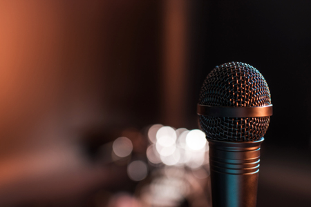 black electric microphone on empty stage