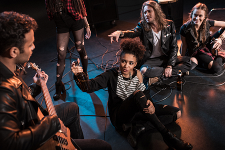 rock and roll band drinking beer after concert on stage