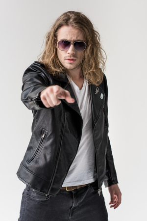 young handsome man in black leather jacket pointing isolated y