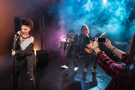 Young woman photographing rock and roll band performing hard rock music