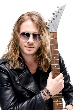 handsome rocker in sunglasses posing with electric guitar isolated on white