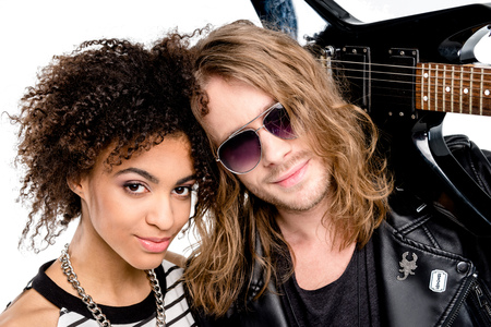 Stylish young couple posing together with electric guitar