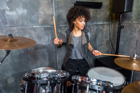rehearse: woman playing drums in musical studio, drummer rock concept