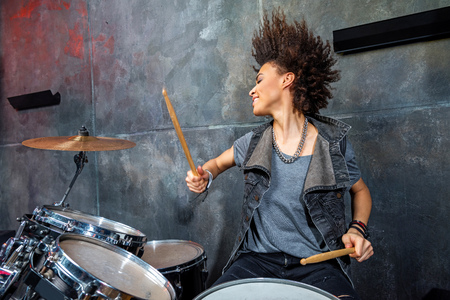 portrait of emotional woman playing drums in studio