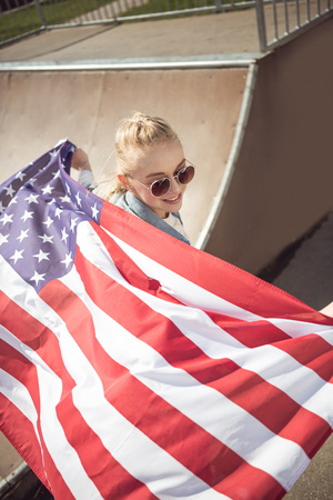 blonde girl in sunglasses holding american flag while standing on ramp at skateboard park Stock Photo