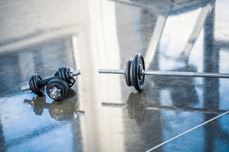 barbell and dumbbells on floor