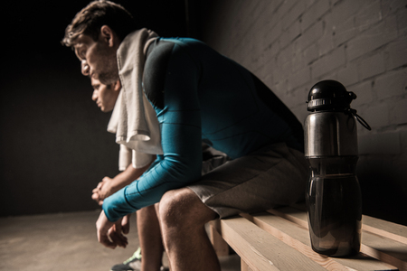male athletes resting at gym locker room Stok Fotoğraf