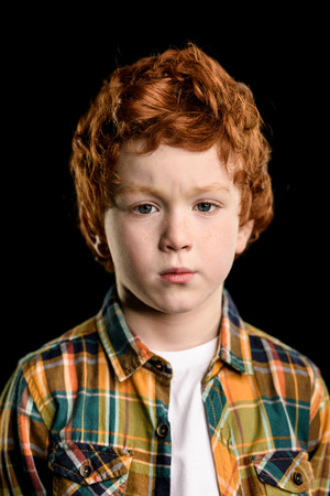 portrait of adorable serious redhead boy looking at camera
