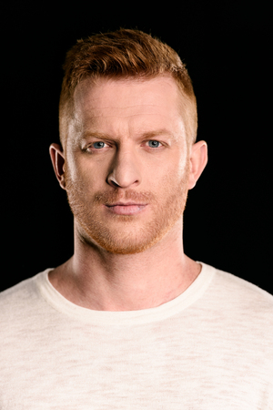 portrait of handsome redhead man posing and looking at camera