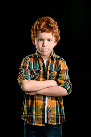 portrait of adorable redhead boy with crossed arms looking at camera